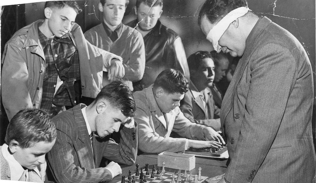 Chess master George Koltanowski had a chess puzzle in The Chronicle for many years. Here he plays several opponents blindfolded in December 1948.