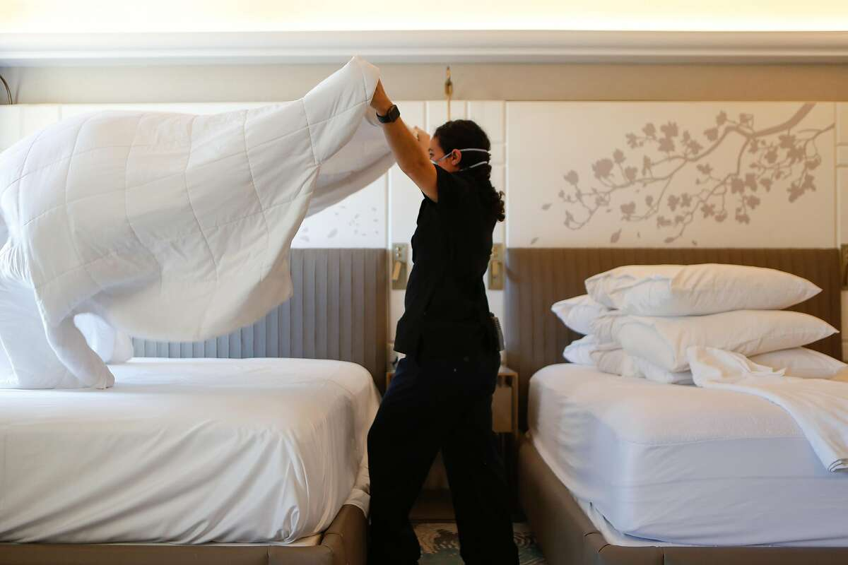 Housekeeper Brenda Vallejo makes a bed in one of the few occupied rooms at Hotel Nikko near Union Square in San Francisco.