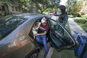 Sean Booth, Houston Chronicle reporter Gwendolyn Wu, and their dog, Birch prepare to take a road trip during the pandemic Thursday, Nov. 19, 2020, in Houston.