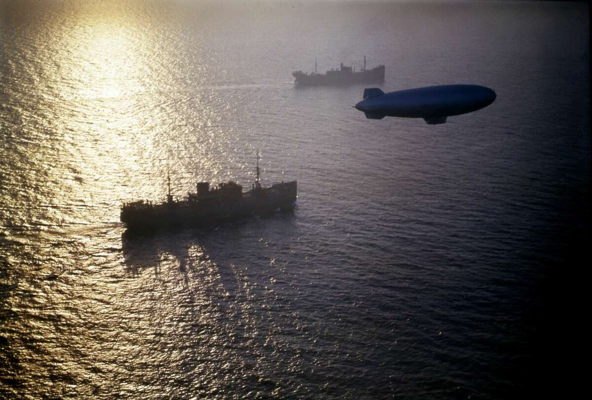 A colorized World War II photograph of two merchant cargo ships from a convoy, escorted by a patrol blimp.