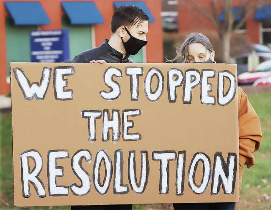 A man and woman hold up a sign Wednesday declaring the Black Lives Matter protest they were attending led to the stopping of a resolution being considered by the Madison County Board to support local police. About 40 to 50 protestors attended the event held on a parking lot near the Madison County Courthouse before the board met. Photo: John Badman | Hearst Newspapers