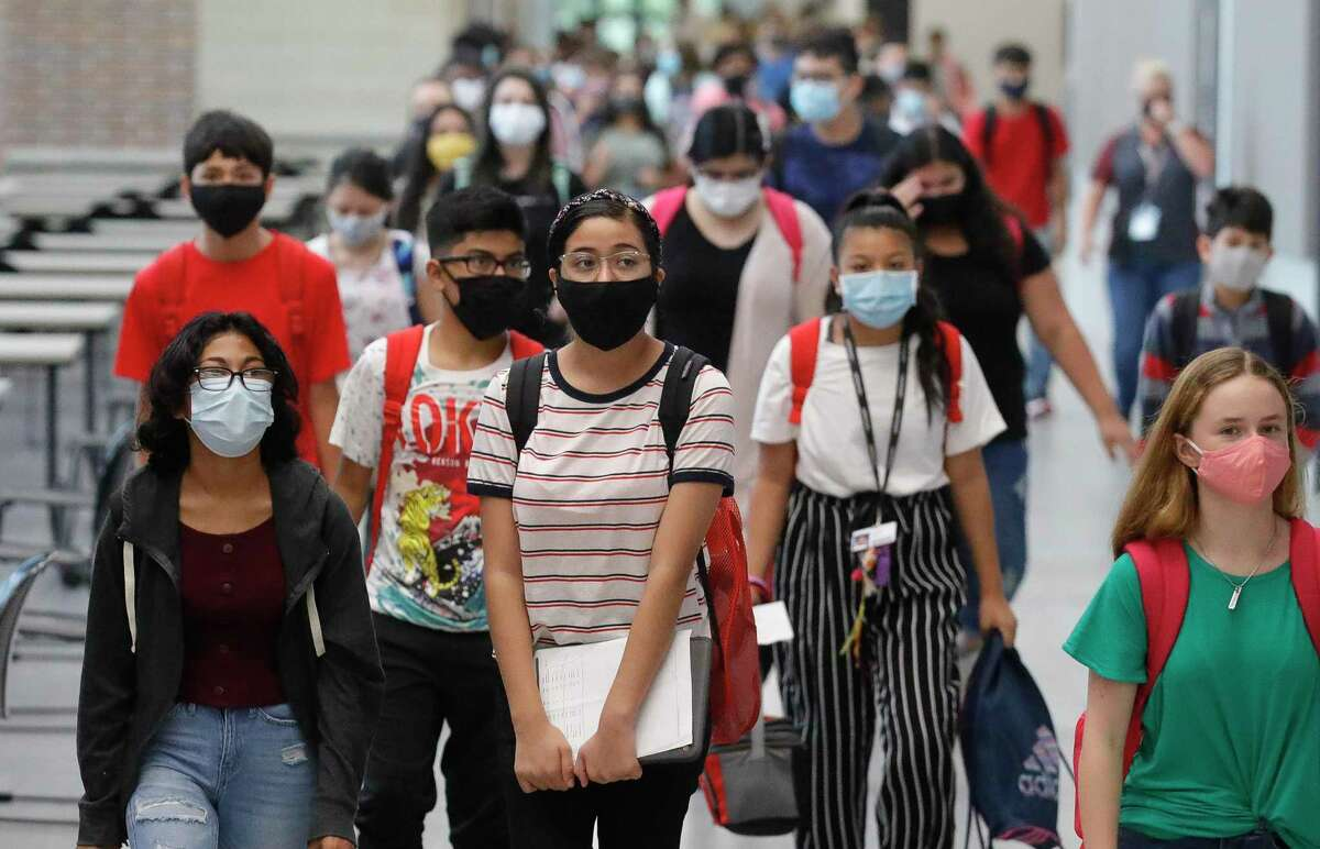 Students wear face masks while walking the hallways of Stockton Junior High School on the first day of in-person school for Conroe ISD on Sept. 8 in Conroe. Conroe ISD officials announced Thursday the district plans to mandate students with COVID-19 isolate but said it was still waiting on the authority to do so.