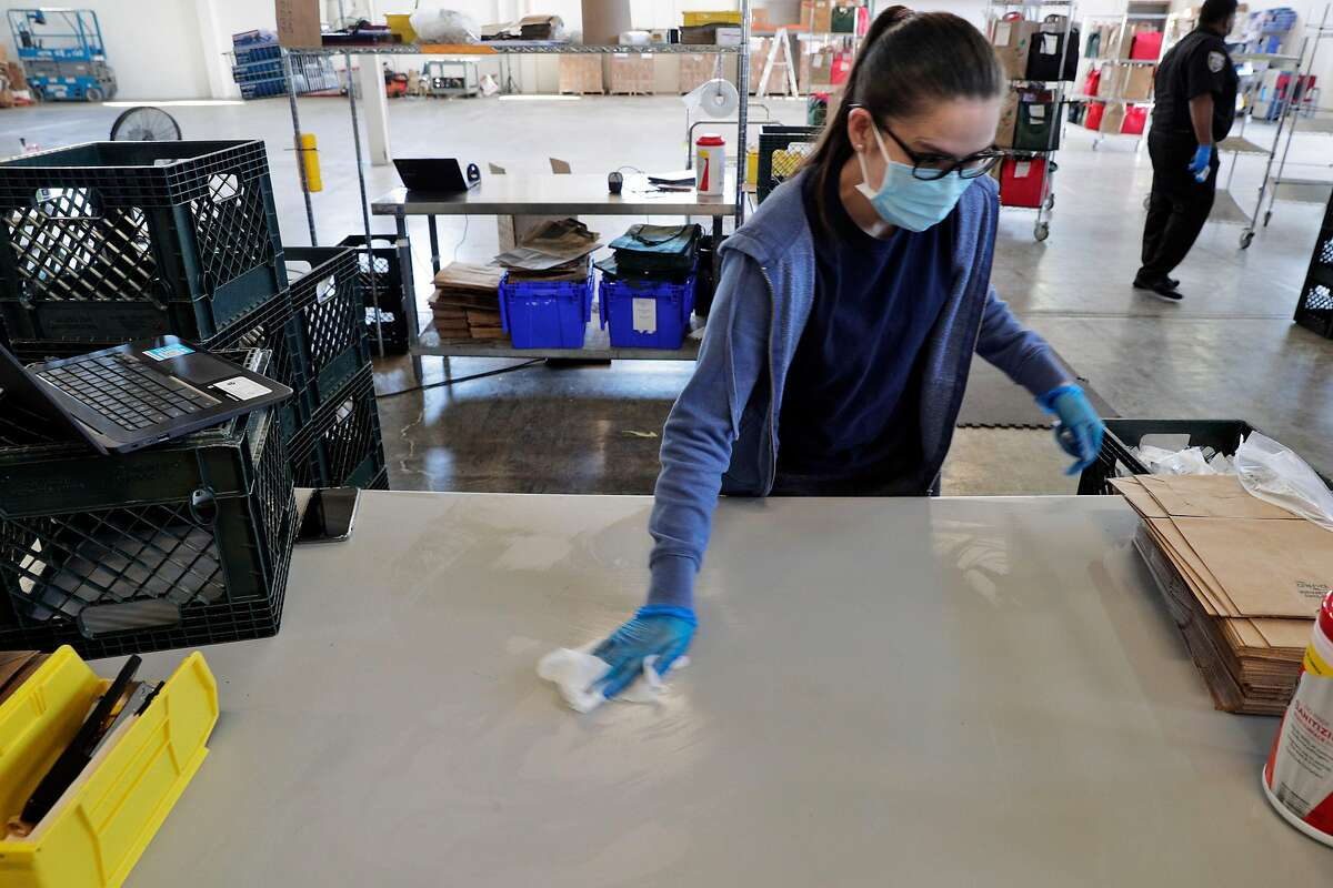 Doreen Rafas disinfects a workspace at the Farmstead Online Grocery warehouse in Burlingame, Calif., on Tuesday, August 11, 2020.