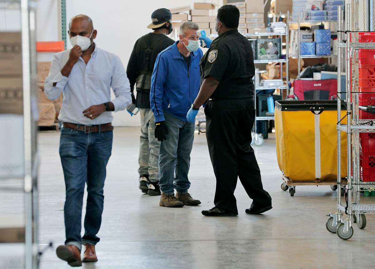 A security guard does a temperature check on an associate, which is done periodically during the day, at the Farmstead warehouse in Burlingame. Many businesses like Farmstead have coronavirus protocols in place already.