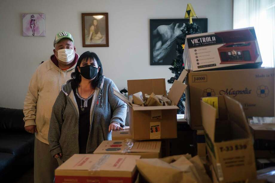 Kimberly Carpenter, right, and Butch Whipple, left, pose for a portrait Tuesday in Carpenter's apartment at Forest Glen Townhomes in Midland. Carpenter and Whipple have both been displaced from their homes at Greenhill Apartments since the structure caught fire in July of 2017. Carpenter began packing her belongings into boxes in October to move back in, before the move-in date was pushed back. (Katy Kildee/kkildee@mdn.net)