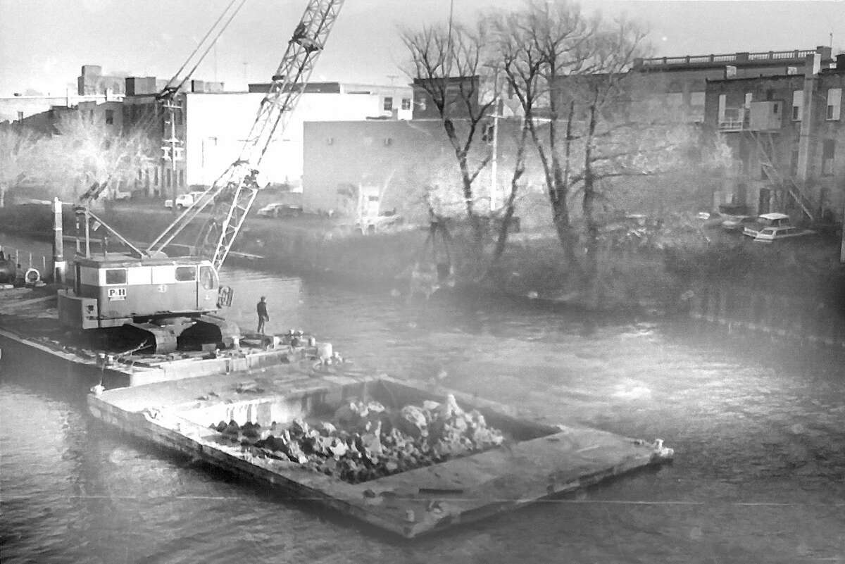 """From the front page of News Advocate on Nov. 20, 1980, """"King Construction Co., of Holland, continued to dredge the Manistee River Channel so that Michigan Bell Telephone could install a new conduit and telephone cables at the bottom of the Manistee River. (Manistee County Historical Museum photo)"""