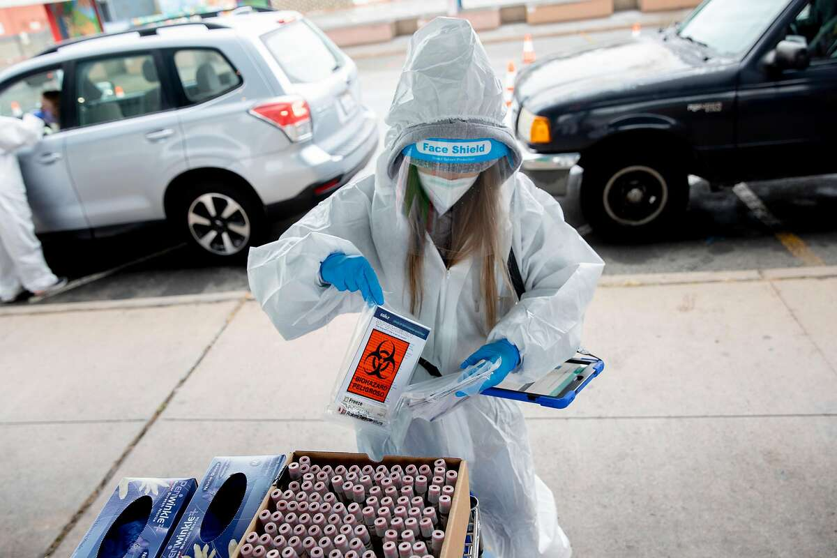 Test site worker Anite Eng wears full PPE while preparing a nose swab kit a newly-opened testing site managed by Color in partnership with the City and County of San Francisco at the Alemany Farmer's Market in San Francisco, Calif. Tuesday, November 17, 2020. San Francisco has ramped up its COVID-19 testing efforts as the county joins dozens of others in moving to more restrictive reopening tiers due to a rise in COVID-19 cases.