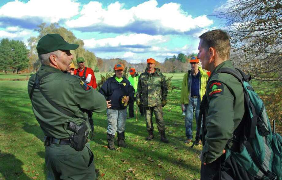 NYS DEC Forest Rangers Tony Goetke, left, and Jamie Laczco, at right, brief members of the Lower Adirondack and Northcountry Search and Rescue teams (background) in this archive image. (John Carl D'Annibale / Times Union) Photo: John Carl D'Annibale / Albany Times Union