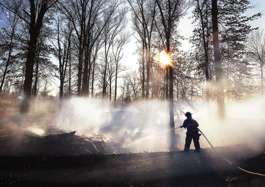 A firefighter sprays down the remains of a shed and what appeared to be an unoccupied mobile home behind 3120 Harris Lane in Fosterburg Thursday afternoon. Two wind-swept brush fires spread in two locations at the same time sending at least 9 area fire departments into action Thursday afternoon. The other fire started in Cottage Hills off Lenora Drive not far from the Cottage Hills VFW about 2 p.m. No injuries were reported in either of the fires but they kept firefighters busy for hours.