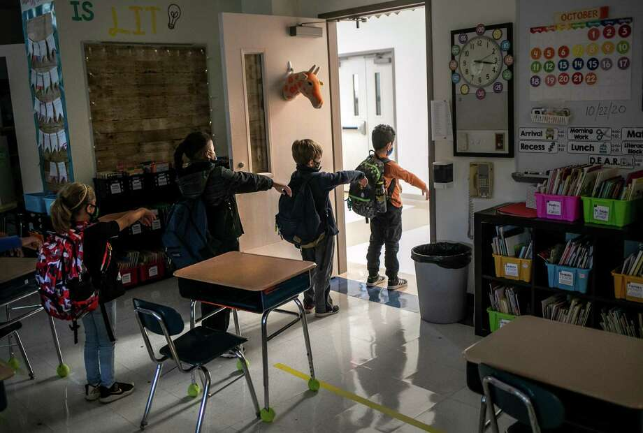 A kindergarten class socially distances while preparing to leave their classroom at Stark Elementary School on October 21, 2020 in Stamford, Connecticut. Stamford Public Schools is continuing the fall semester with a hybrid model of in-class and distance learning, occasionally quarantining individual classes when a student or faculty member tests positive for COVID-19. Photo: John Moore / Getty Images / 2020 Getty Images
