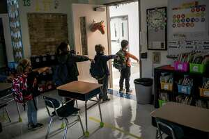A kindergarten class socially distances while preparing to leave their classroom at Stark Elementary School on October 21, 2020 in Stamford, Connecticut. Stamford Public Schools is continuing the fall semester with a hybrid model of in-class and distance learning, occasionally quarantining individual classes when a student or faculty member tests positive for COVID-19.
