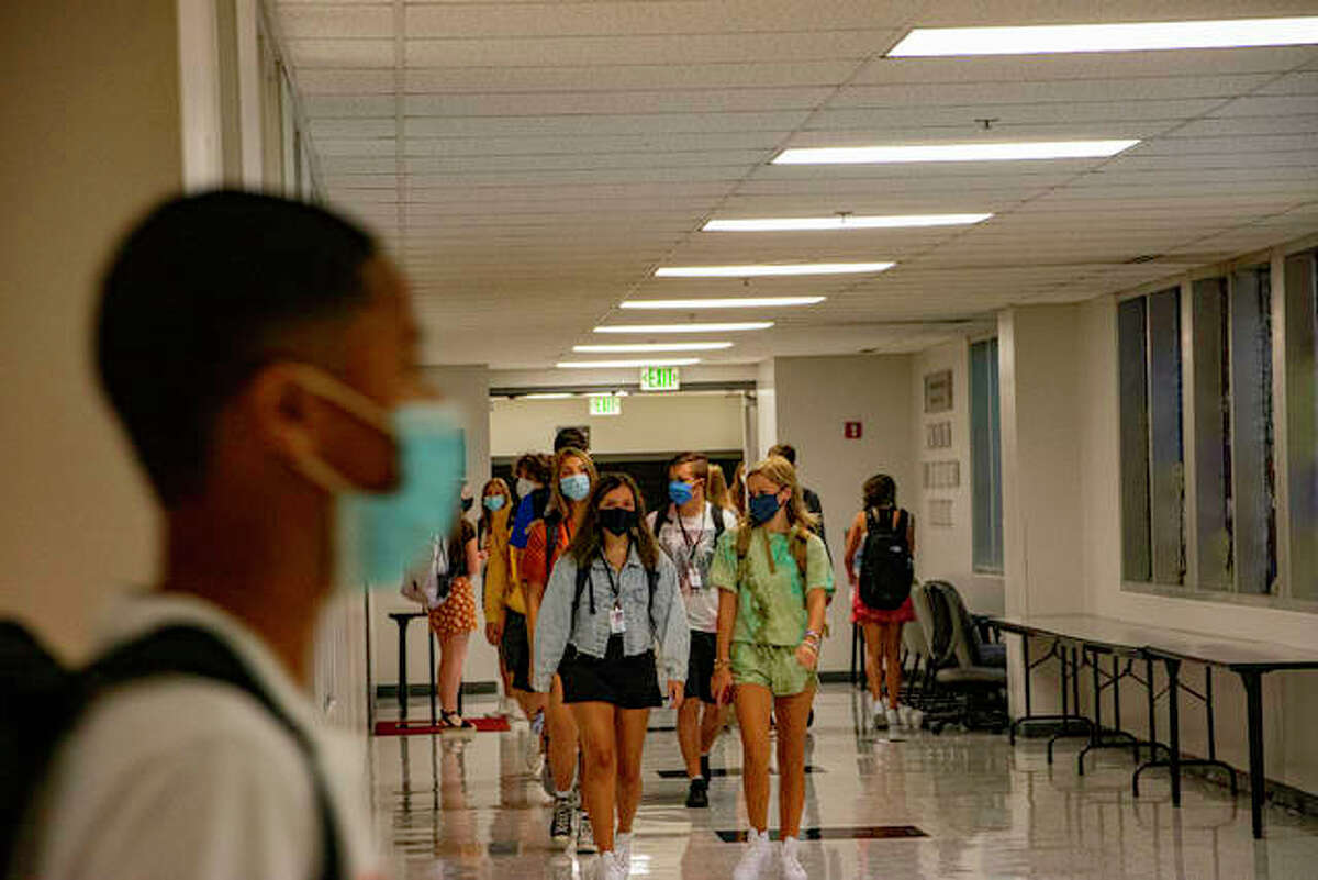 In this August 2020 file photo, Edwardsville High School students walk the school halls with masks as their first day back looks different.
