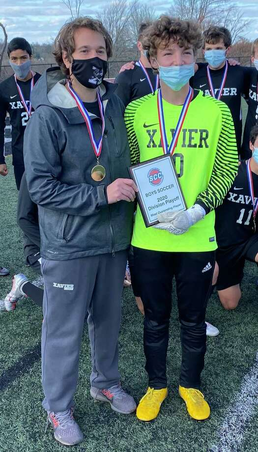 Xavier coach Brian Fitzgerald and Outstanding Player goalkeeper Spencer Misenti. The goalkeeper was named the SCC-A tournament's Most Outstanding Player, recording four saves in a 2-1 win over Cheshire in the championship game this week. Photo: Dave Phillips / For Hearst Connecticut Media