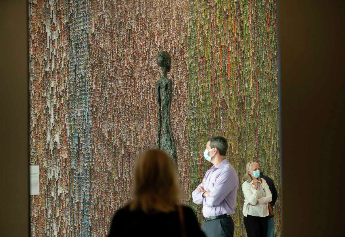 A wall comprised of tiny photos and a sculpture by Giacometti inside The Museum of Fine Arts Houston's new Nancy and Rich Kinder Building on Wednesday, Nov. 18, 2020, in Houston.