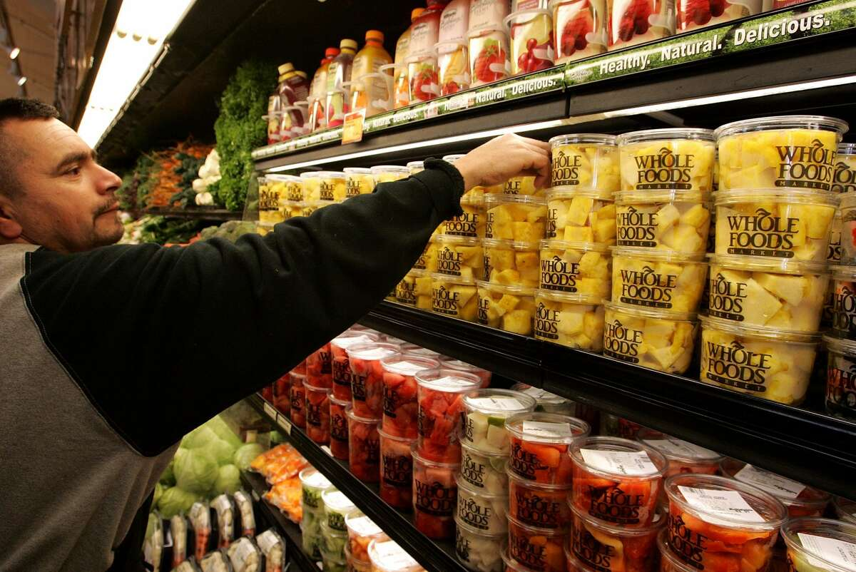 Whole Foods employee Cesar Martinez arranges shelves of fresh pineapple at a Whole Foods Market on February 22, 2007 in San Francisco, California.