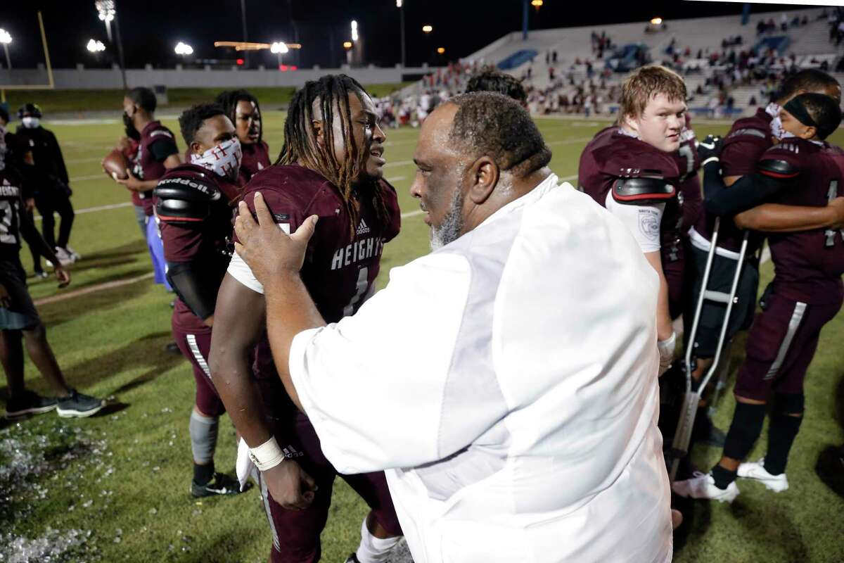 Heights Bulldogs head coach Stephen Dixon Sr., right, reaches out to hug a teary eyed Kendric Rhymes, left, as they celebrate after Rhymes' two point conversion score to win 22-21 in overtime against the Lamar Texans after a high school football game at Delmar Stadium Friday, Nov. 13, 2020 in Houston, TX. Lamar had won 72 games in district play for over 10 years until tonight's upset.