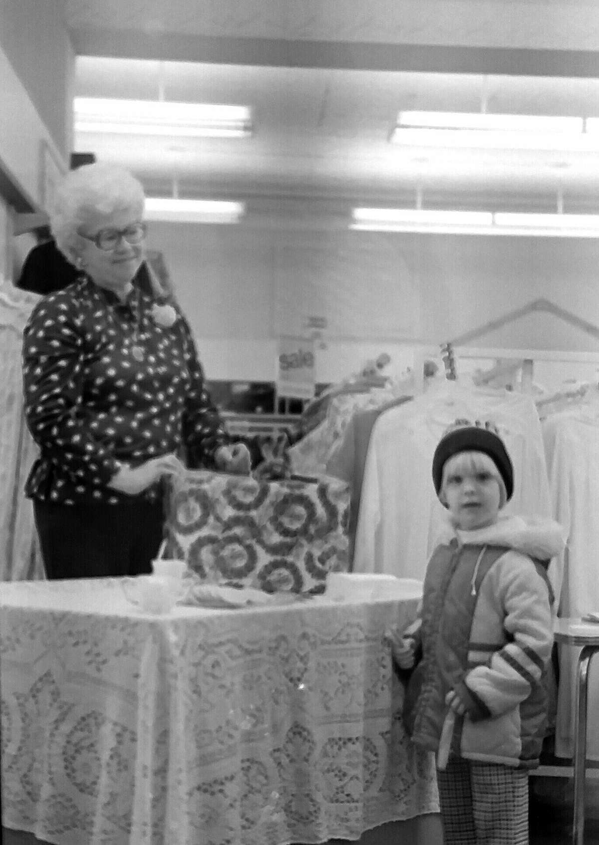 """From the Nov. 21, 1980 issue of the News Advocate, """"J.C. Penney is celebrating a grand 're-opening' in honor of the store's recent refurbishing efforts. Store employee Helen Colton smiles as small customer Laura Merritts ponders the choice between a free sucker and a free cookie. The gift box holds names to be drawn for two free gift certificates."""" (Manistee County Historical Museum photo)"""