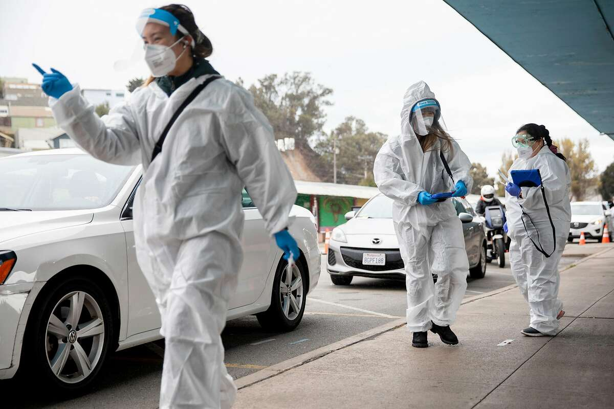 Workers Alexis Balomaga (left), Anita Eng and Patricia Ruiz direct cars between administering nose swabs for coronavirus tests at the Alemany Farmers' Market in San Francisco.