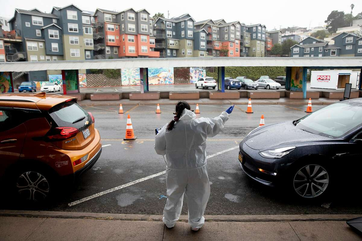 Test site worker Patricia Ruiz directs vehicles to move forward at a newly-opened testing site at the Alemany Farmer's Market in San Francisco, November 17, 2020.