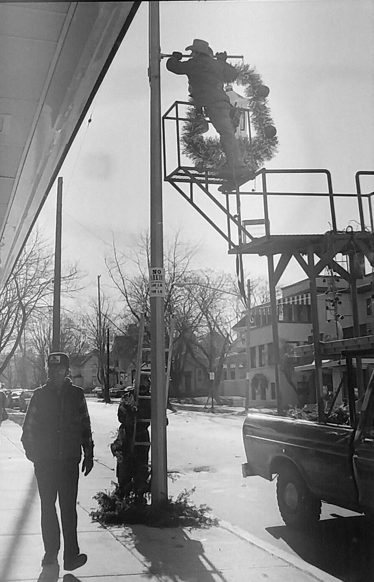 Christmas decorations adorning the streetlight poles in Manistee signal the approach of the Yuletide season. An employee of Mid-Michigan Displays is shown hanging one of the many wreaths decorating downtown Manistee in November 1980. (Manistee County Historical Museum photo)