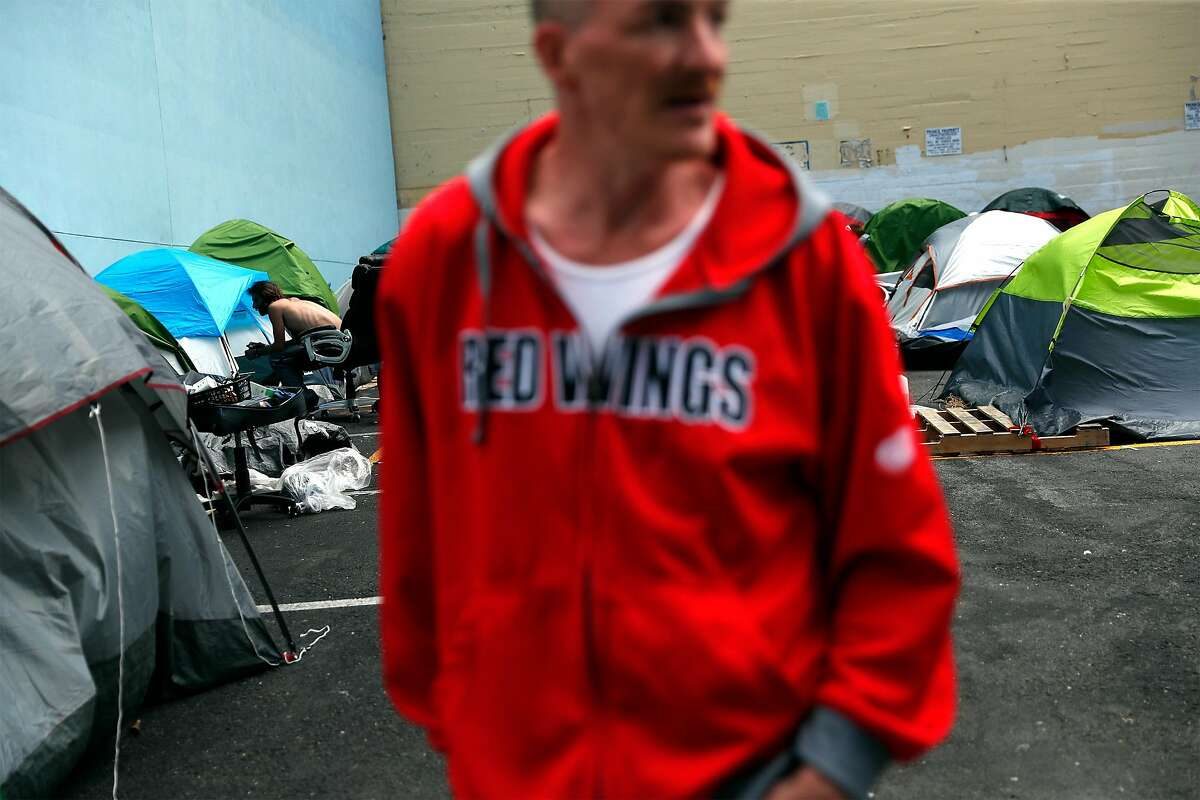 Richard van Dusen stands outside his tent in the parking lot at 180 Jones St. in San Francisco in June.