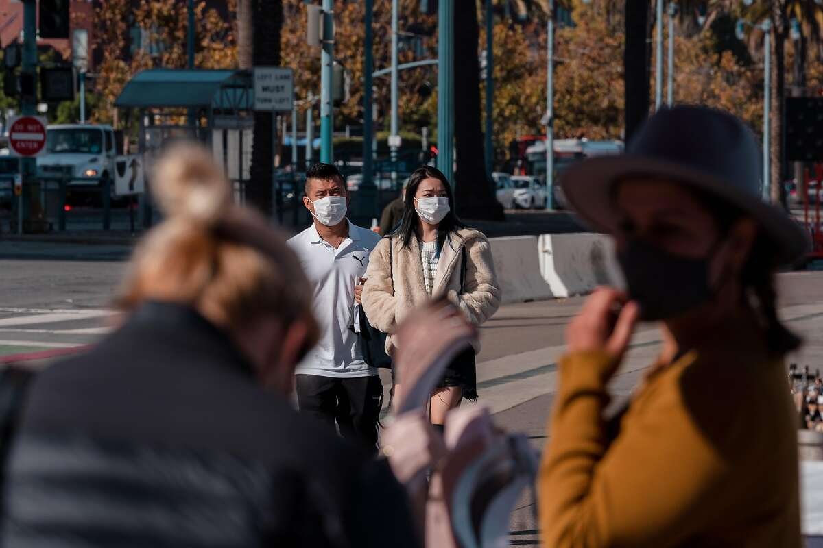 People walk along the Embarcadero in San Francisco, Calif., on Thursday, November 19, 2020.