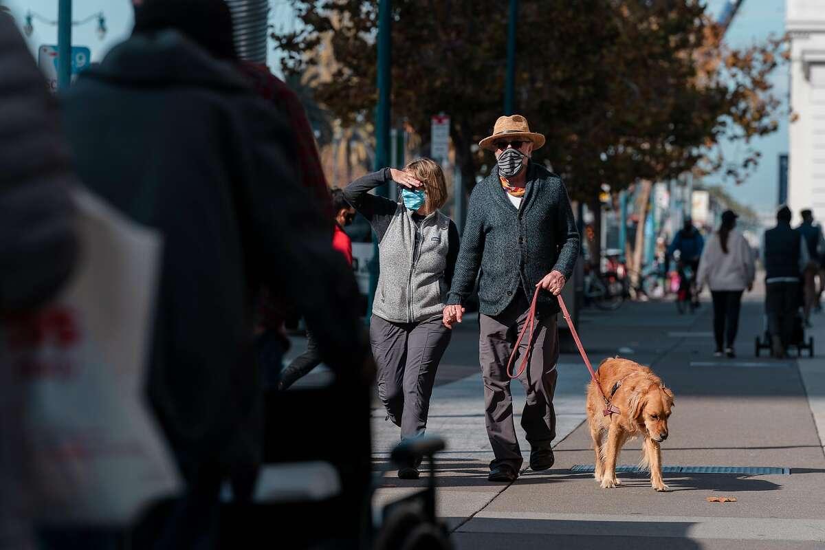 A couple walks their dog along the Embarcadero in San Francisco, November 19, 2020.