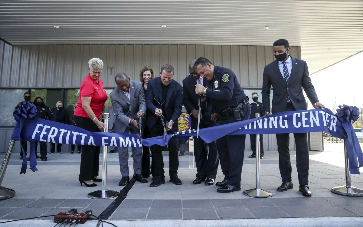Houston City Councilmember Carolyn Evans-Shabazz, from front left, Mayor Sylvester Turner, Tilman Fertitta, former Houston Police Chief Charles McClelland, current HPD Chief Art Acevedo and Councilmember Edward Pollard struggle to cut the ribbon during a ceremony to unveil the new HPD training center Thursday, Nov. 19, 2020, at the Tilman Fertitta Family Tactical Training Center in Houston.
