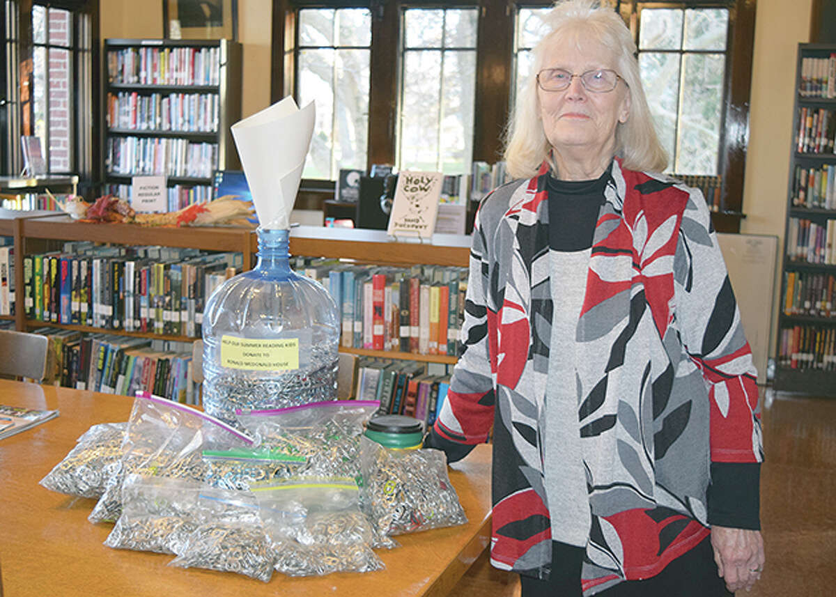 Darlene Smith, director of Winchester Public Library, stands next to the collection of soda can tabs collected during the past year. There are around 3 gallons of tabs, which will be donated to the Ronald McDonald House in Springfield.