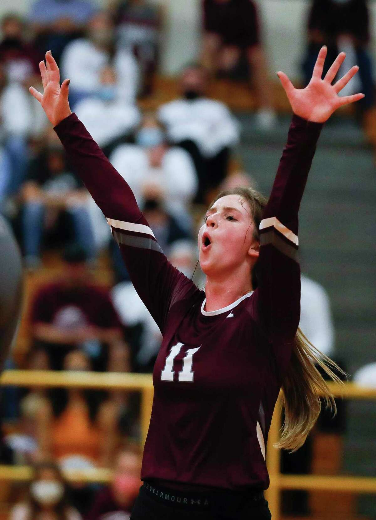 Magnolia setter Faith Lynch (11) react after a block during the first set of a Region III-5A bi-district high school volleyball playoff match at Klein Oak High School, Thursday, Nov. 19, 2020, in Spring.