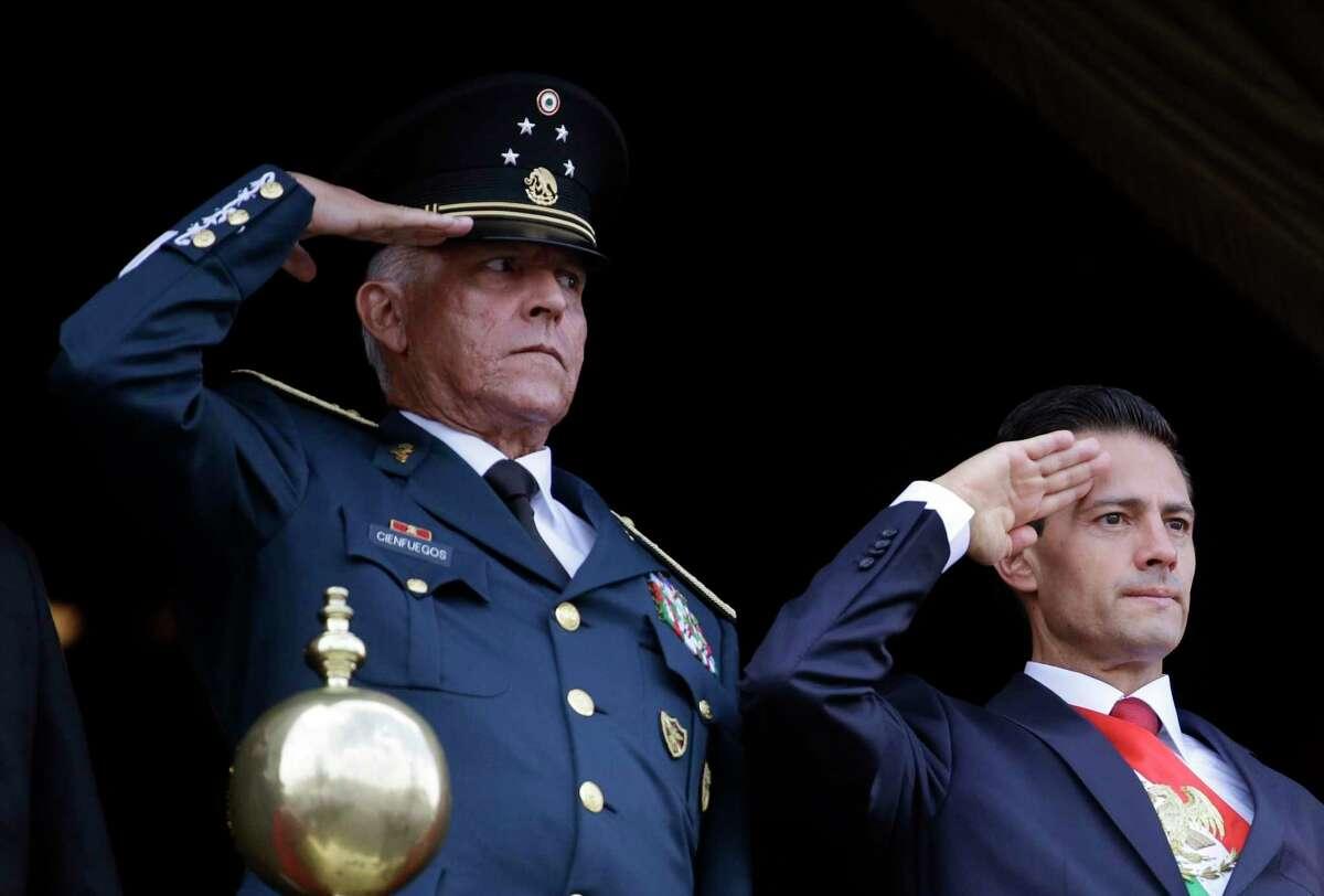 En esta fotografía de archivo del 16 de septiembre de 2016, el secretario de la Defensa, general Salvador Cienfuegos, a la izquierda, y el presidente de México, Enrique Peña Niego, hacen el saludo durante el desfile de la Independencia en la principal plaza de la Ciudad de México.