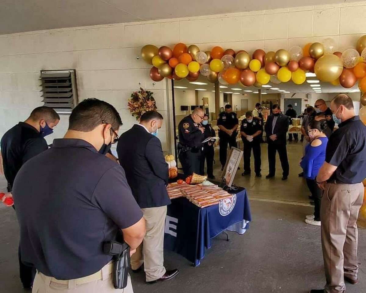 Laredo police officers share a moment of prayer moments before their Annual Laredo Police Thanksgiving Luncheon. This year, the event went curbside.