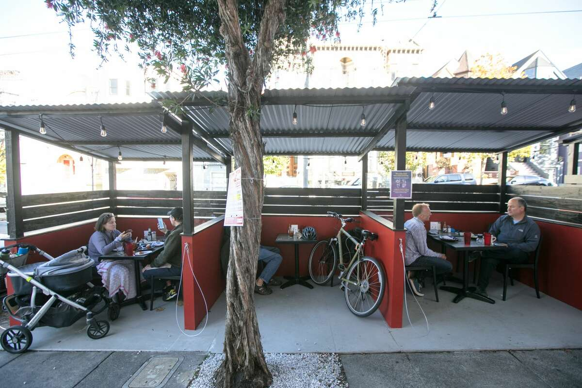Customers eat at parklets in front of Brenda's Meat and Three on Divisadero Street in San Francisco on Nov. 19, 2020. Like many other restaurants, Brenda's has been severely affected by the COVID-19 coronavirus pandemic.