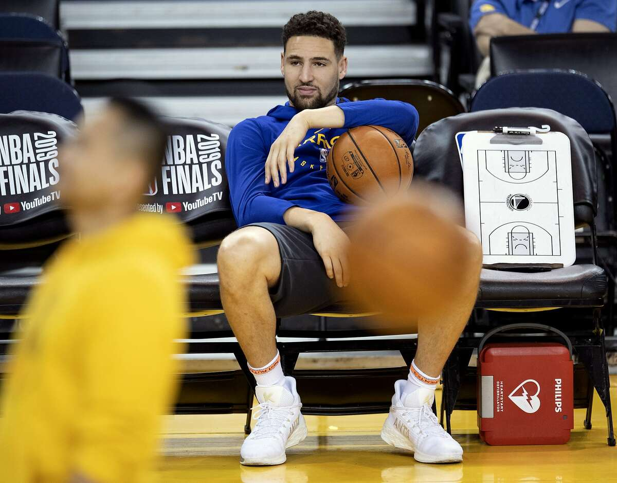 In this June 4, 2019, file photo, Golden State Warriors' Klay Thompson sits on the bench watching teammates during practice for the NBA Finals against the Toronto Raptors in Oakland, Calif. The Warriors said Thursday, Nov. 19, 2020, that Thompson has suffered a torn right Achilles tendon and is expected to miss the upcoming season. Thompson was injured during a pickup game in Southern California the day before.