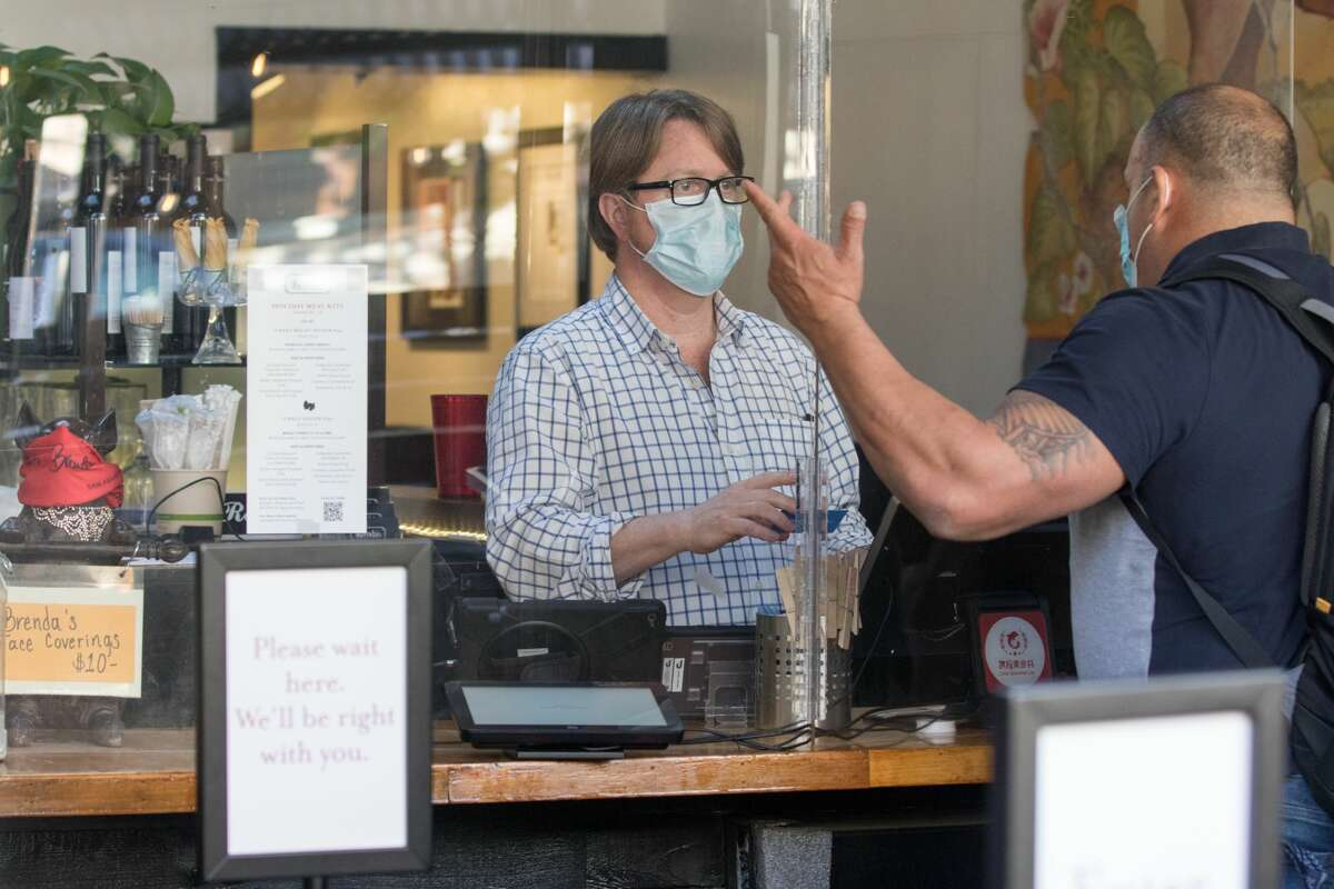 General Manager Hunter Alexander handles an order behind a sneeze guard at Brenda's Meat and Three on Divisadero Street in San Francisco on Nov. 19, 2020. Like many other restaurants, Brenda's has been severely affected by the COVID-19 coronavirus pandemic.