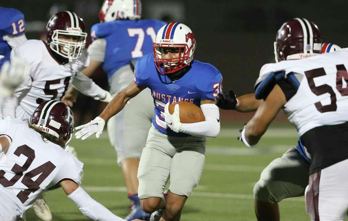 Mustang running back Joel Lozano looks for running room amidst converging Owl defenders as Highlands plays Jefferson in high school football at Alamo Stadium on Nov. 19, 2020
