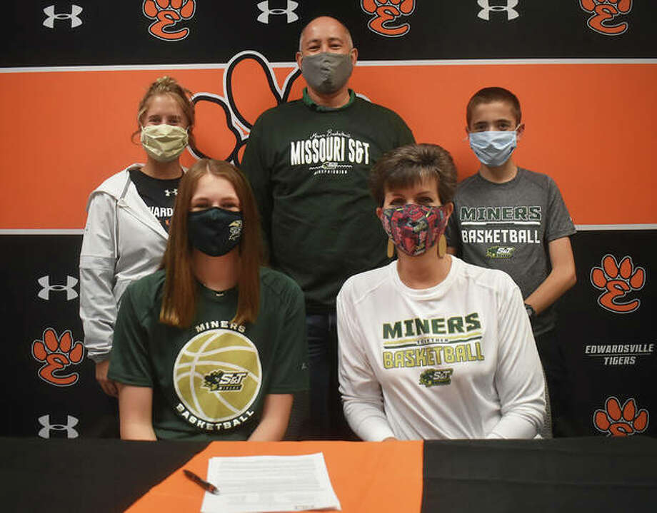 Edwardsville senior Katelynne Roberts, seated left, will play college basketball at Missouri S&T. She is joined by her family and EHS coach Caty (Ponce) Happe. Photo: Matt Kamp The Intelligener