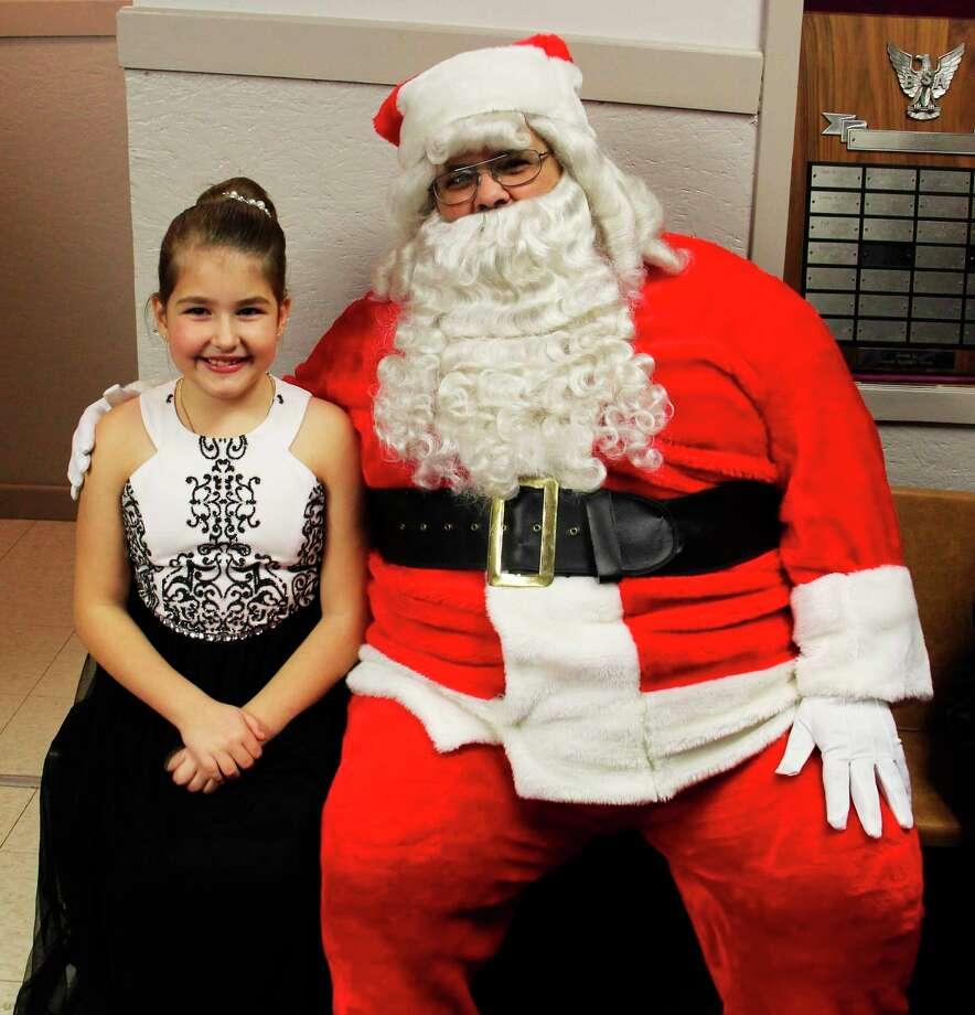 Crowned Snow Princess Rylee Steinman, 8, smiles big with Santa in Elkton last year.