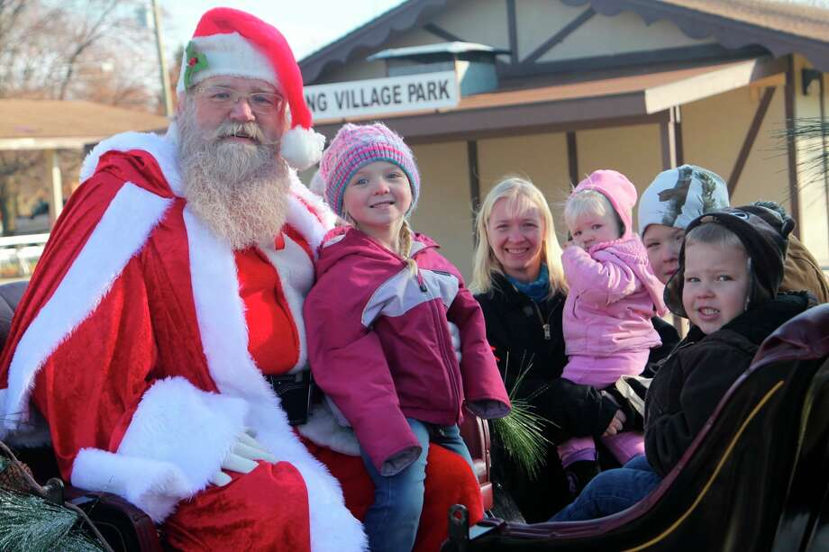 The Deming family sits with Santa on his sleigh during last year's Spirit of Christmas event.