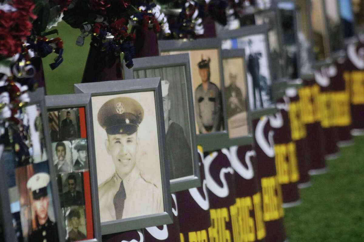 Pictures of veterans adorn the Deer Park varsity cheerleaders' megaphones during the team's home game leading up to Veterans Day.