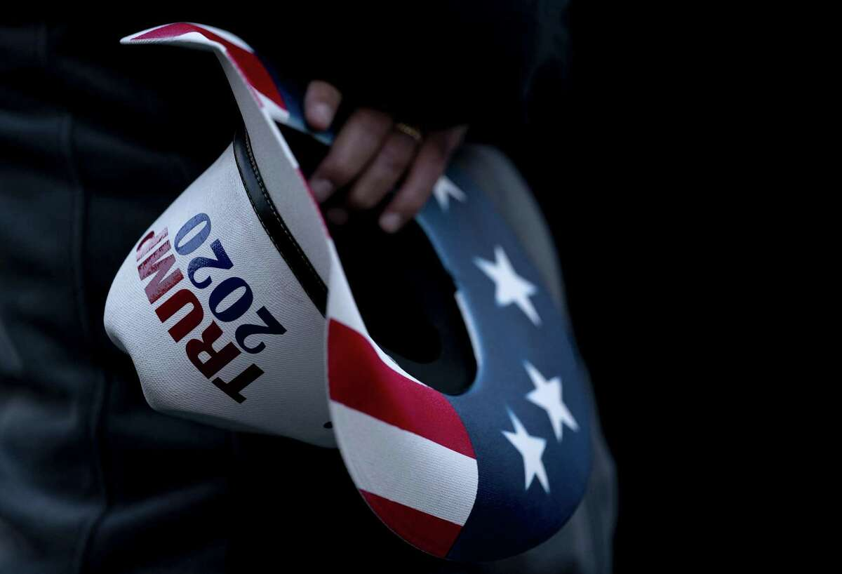 A demonstrator holds a Trump 2020 hat at Black Lives Matter plaza near the White House in Washington, D.C., U.S., on Friday, Nov. 13, 2020. The Trump administration is stepping back from negotiations on a new stimulus package and leaving it to Senate Majority LeaderMcConnellto revive long-stalled talks with House Speaker Pelosi, according to two people familiar with the matter. Photographer: Stefani Reynolds/Bloomberg