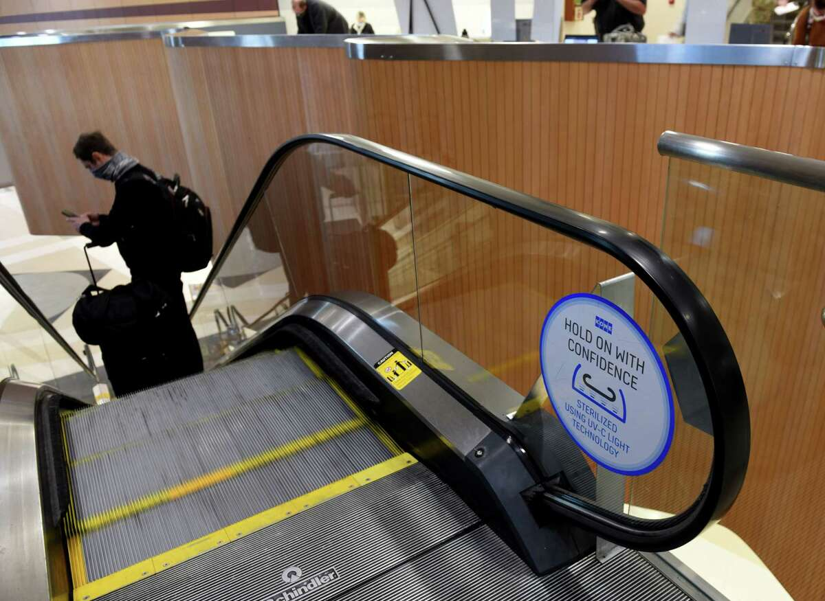 Escalator sanitization signs are visible as a passenger heads toward baggage claim after arriving at Albany International Airport on Thursday, Nov. 19, 2020, in Colonie, N.Y. (Will Waldron/Times Union)