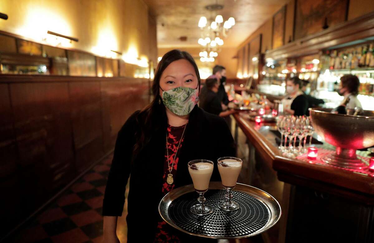 Manager Samantha McGrath holds cappucinos for guests seated outside at Tosca Cafe, where dinner service has resumed.