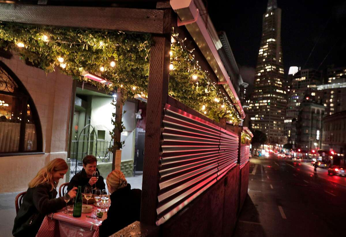 Customers enjoy dinner at the beloved Tosca Cafe in San Francisco, which, after being closed for more than a year and now under new ownership, has reopened for outdoor dining with an elaborate parklet.