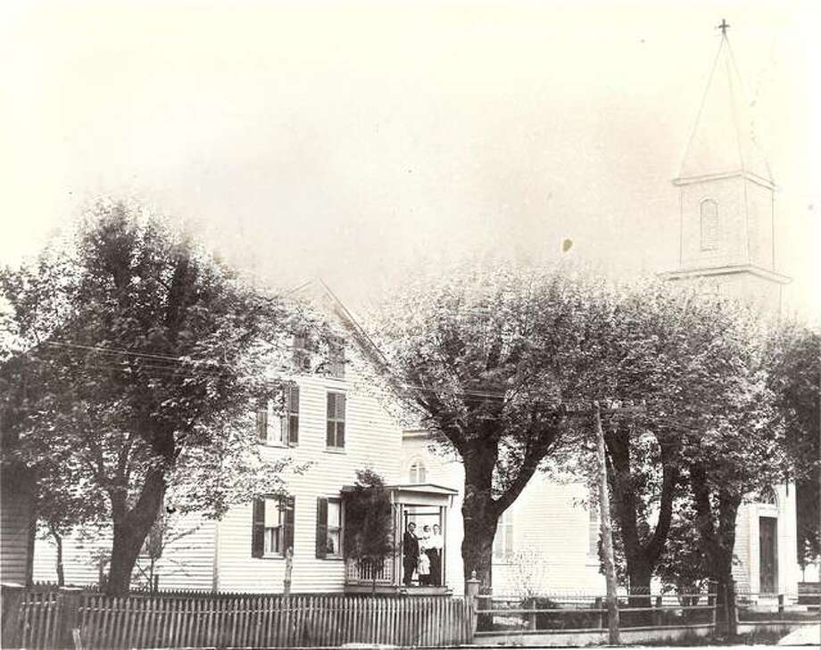 This photo from about 1908 shows St. John's Evangelical Church in Brighton on the right and the parsonage on the left, with then pastor Rev. Erdman Richter and his family standing on the parsonage porch. The church was built in 1870 and parsonage around 1880.