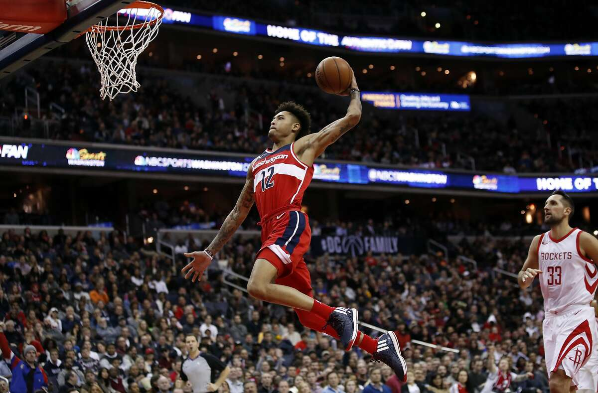 Washington Wizards forward Kelly Oubre Jr. (12) goes for a dunk past Houston Rockets forward Ryan Anderson (33) during the second half of an NBA basketball game Friday, Dec. 29, 2017, in Washington. The Wizards won 121-103. (AP Photo/Alex Brandon)
