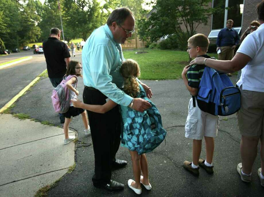 Principal Frank Arnone gets a hug from 4th grader Chloe Girard, 8, as he greets students on the first day of school at Holland Hill School on Thursday, September 2, 2010. Photo: Brian A. Pounds / Connecticut Post
