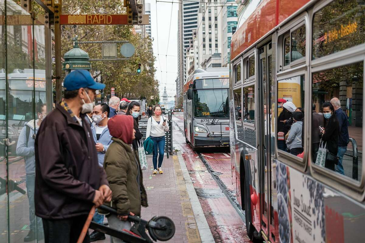 Passengers wait to board a bus on Market Street in San Francisco on Wednesday. The Metropolitan Transportation Commission voted unanimously Friday to scrap a controversial mandate requiring large companies to keep 60% of workers at home in an effort to reduce greenhouse gas emissions and will instead cap some car commuters.