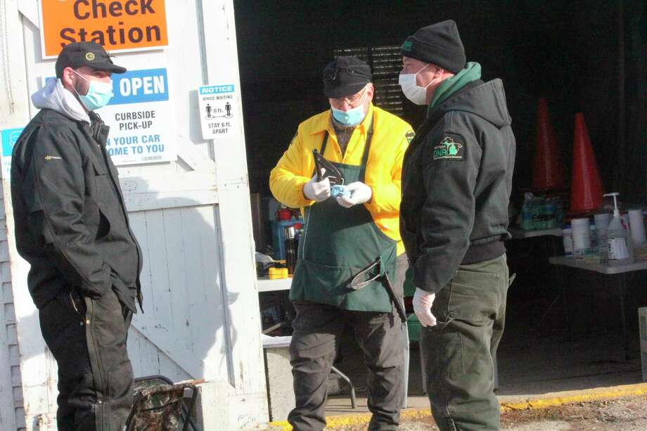 DNR wildlife biologist Pete Kailing (center) gets ready to check deer with other personnel on Wednesday at the DNR check station in Paris. (Pioneer photo/John Raffel)