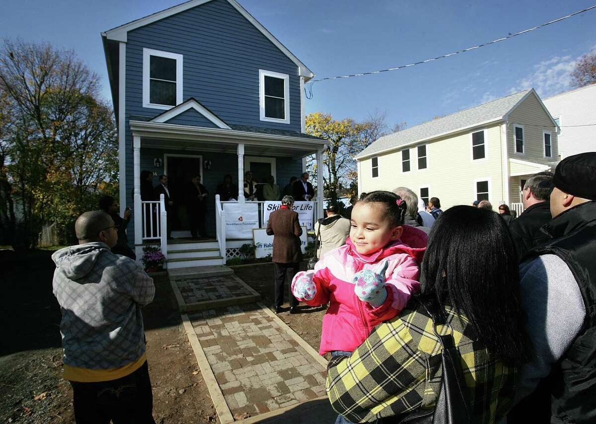 Peter Casolino Cas091107 11/07/09 New Haven-- Janet Ayala and her 2-yearold Daughter Brianna (Ayala) attend the Habitat for Humanity Dedication Ceremony for organization's newest city home at 34 Dewitt Street. The Ayala family is friend's with the home's new owner, Marisol Morales. Photo -Peter Casolino **